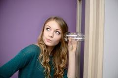 Jonge blondevrouw die binnen aan een gesprek met een glas luisteren stock foto's