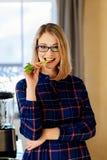 Jonge blondevrouw die groene selderie in keuken eten stock afbeelding