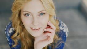 Jonge blondevrouw die met blauwe ogen de camera onderzoeken Portret met positieve emoties stock footage