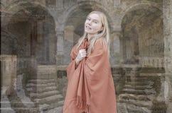 Jonge blondevrouw die met met kasteel op achtergrond glimlachen Stock Afbeeldingen
