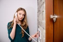 Jonge blondevrouw die op de intercom spreken stock foto