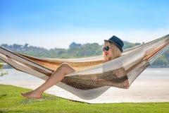 Jonge blondevrouw die op hangmat rusten stock afbeelding