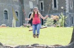 Jonge blondevrouw die op houten schommeling dichtbij oud kasteel in Na glimlachen Royalty-vrije Stock Foto's