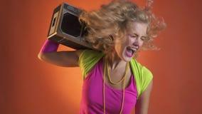 Jonge blondevrouw die pret hebben die met boombox, retro stijl dansen stock footage