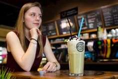 Jonge blondevrouw in lokale koffie bij houten wi van de lijstdrank frappe Royalty-vrije Stock Foto