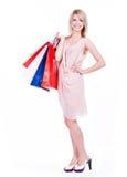 Jonge blondevrouw met kleurrijke het winkelen zakken stock fotografie