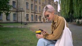 Jonge blondevrouw in zonnebril met de korte koffie van de haarholding en het typen op telefoon, die dichtbij universiteit zitten stock footage