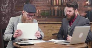 Jonge blondezakenman met modieuze baard en zijn partner op een vergadering stock video