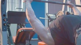 Jonge bodybuilder die bankpers doen stock videobeelden