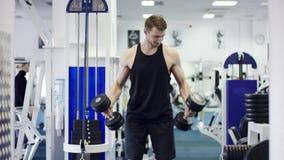 Jonge bodybuilder die met domoren in een gymnastiek uitoefenen stock footage
