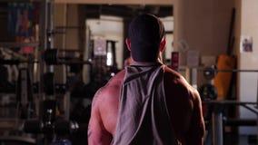 Jonge bodybuilder opleiding in een gymnastiek stock videobeelden