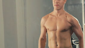 Jonge bodybuilder opleiding met de ladingen voor wapensspieren in gymnastiek langzaam stock footage