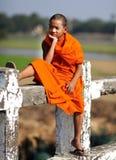 Jonge Boeddhistische monnikszitting op een brug Stock Foto's