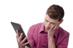 Jonge bored mens het houden van een tablet. Stock Fotografie