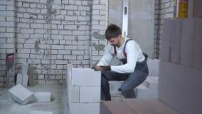 Jonge bouwer die gelucht concreet blok leggen en het controleren met bellenniveau stock video