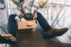Jonge in brand gestoken zakenmanzitting op vloer met bezittingen in doos royalty-vrije stock foto