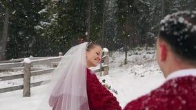 Jonge bruid die aan bos lopen die bruidegom vragen om haar te volgen en pret te hebben bij rancho onder zware sneeuwval Het huwel stock videobeelden