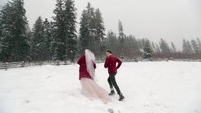 Jonge bruid die aan bos lopen die bruidegom vragen om haar te volgen en pret te hebben bij rancho onder zware sneeuwval Het huwel stock footage