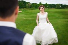 Jonge bruid die haar bruidegom op een weide lopen te ontmoeten royalty-vrije stock afbeeldingen