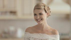 Jonge bruid in een kleding die van het kanthuwelijk lachen bij stock footage
