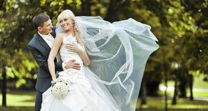 Jonge bruid en bruidegom die en aan elkaar lachen kijken Stock Fotografie