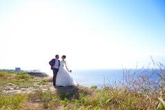 Jonge bruid en bruidegom die op de kust lopen Royalty-vrije Stock Foto
