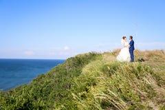 Jonge bruid en bruidegom die op de kust lopen Stock Foto's
