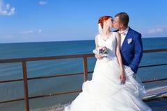Jonge bruid en bruidegom die op de kust lopen Royalty-vrije Stock Fotografie