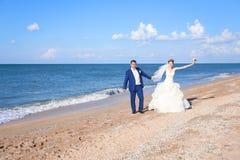 Jonge bruid en bruidegom die op de kust lopen Royalty-vrije Stock Afbeelding