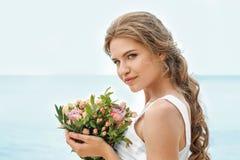Jonge bruid in het witte boeket van de togaholding Royalty-vrije Stock Afbeelding