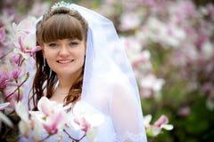 Jonge bruid onder de bloemen Stock Afbeeldingen