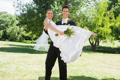 Jonge bruidegom opheffende bruid in wapens bij tuin Stock Fotografie