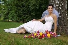 Jonge bruidzitting onder boom stock foto's