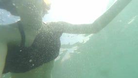 Jonge bruin-haired vrouw onderwater met zwemmend masker die aan actiecamera, het duiken zonder aqualong en het maken kijken stock videobeelden