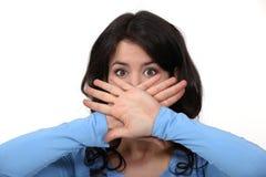 Jonge brunette die haar mond verbergen Stock Afbeeldingen