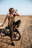 Jonge brutale mensenzitting op zijn motorfiets en drinkwater stock afbeelding