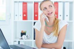 Jonge bureauvrouw die op de mobiele telefoonzitting spreken in het bureau Stock Foto's