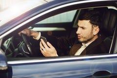 Jonge bussinesman in kostuum spreekt telefonisch in zijn auto De zaken zien eruit Testaandrijving van de nieuwe auto royalty-vrije stock fotografie