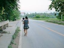 Jonge carekess Aziatische moeder die haar vervoeren weinig dochter en op de straat lopen royalty-vrije stock foto