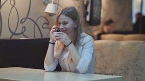 Jonge charmante meisjeszitting bij koffie terwijl het ontspannen, het drinken koffie van een kop en het spreken op de telefoon stock footage