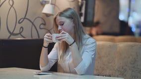 Jonge charmante meisjeszitting bij koffie terwijl het ontspannen, het drinken koffie van een kop en het spreken op de telefoon stock videobeelden