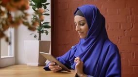 Jonge charmante moslimvrouw in het blauwe hijab typen op tablet en het glimlachen bij camera, die in koffie, mooi wijfje zitten m stock footage