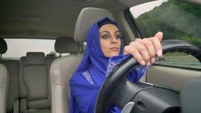 Jonge charmante moslimvrouw in hijab die een auto op de weg drijven stock videobeelden