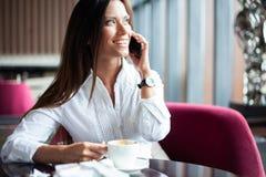 Jonge charmante vrouw die met smartphone roepen terwijl het zitten alleen in koffiewinkel tijdens vrije tijd, aantrekkelijk wijfj stock afbeelding