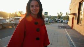 Jonge charmante vrouw die rond de stad bij zonsondergang en het glimlachen lopen stock videobeelden