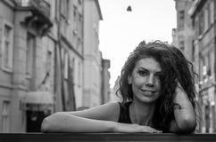 Jonge charmante vrouw met lang krullend haar, die onder de oude stad van Lviv-architectuur in sexy zwarte kleding wandelen royalty-vrije stock foto's