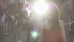 Jonge charmante vrouw met zich op straat tijdens festival bevinden, in camera en gemberhaar die, menigte van ventilators kijken d stock video