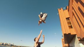 Jonge cheerleaderstraining in openlucht bij cityscape op achtergrond - jonge mens die het meisje houden die tik in de lucht uitvo stock video