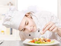 Jonge chef-kok die heerlijke salade verfraait Stock Afbeelding