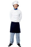 Jonge chef-kok die zich met erachter handen bevinden Stock Afbeelding